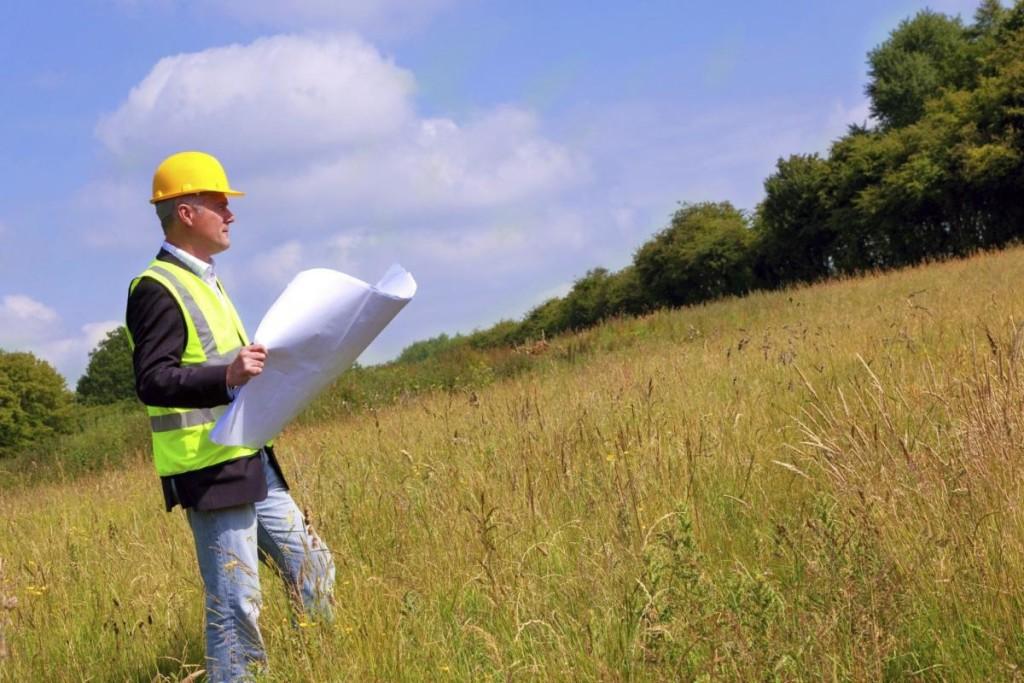 Мужчина с документами стоит на земельном участке
